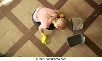 woman cleaning the floor. girl in gloves cleans the kitchen...