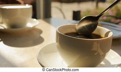 Hand Stirring Steaming Cup of Black Coffee. coffee house -...