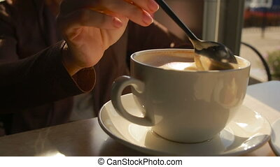 Woman mixing mousse from the coffee and eating it. close up...