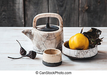 Old ceramic kettle with quinces and dried pears on wooden...