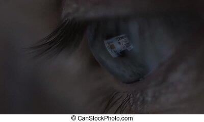 Close-up of beautiful young man eyes looking at monitor,...
