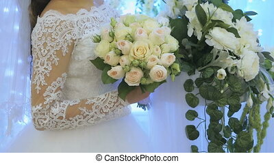 The bride standing next to arch of flowers indoors - The...