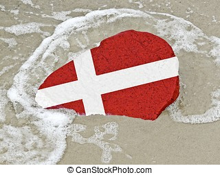 Flag of Denmark on a stone on the beach of the Baltic Sea -...