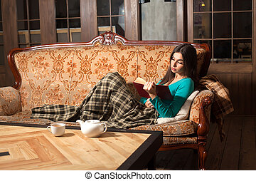 Interested in red bok - Woman is reading a book on the...