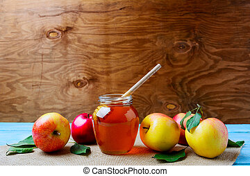 Glass honey jar with dipper and fresh apples, copy space....