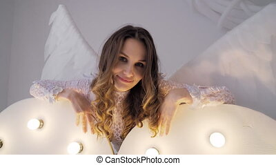 The girl in a white dress with wings near the glowing...