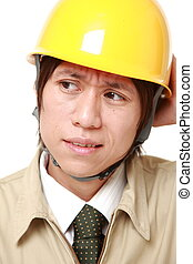 perplexed construction worker - studio shot of Japanese...