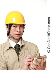 Japanese construction worker writing in notebook - studio...