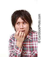perplexed man - portrait of young Japanese man on white...
