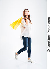 Full length portrait of an attractive woman holding shopping...