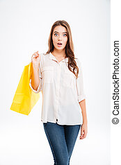 Portrait of a surprised woman holding shopping bag isolated...