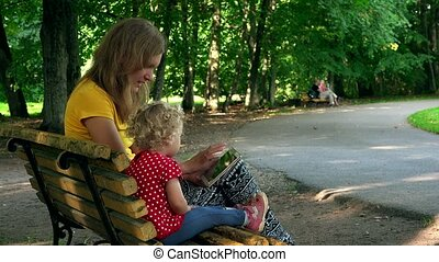 woman with little girl using tablet computer sit on bench in park