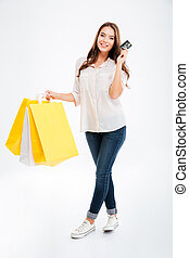 Happy young woman holding shopping bags and bank card - Full...