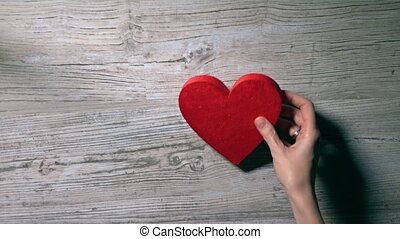 Girl placing two red hearts on a wooden table, top view....
