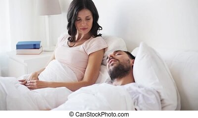 angry woman waking man sleeping in bed - people, snore and...