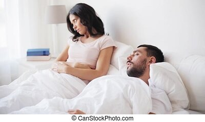 angry woman waking man sleeping in bed