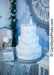three-layer white holiday cake on the table decorated with fir trees and gift box