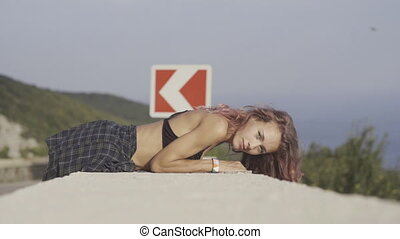 Sensual girl with pink hair lying on the parapet overlooking...
