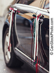 Black Mercedes-car decorated with ribbons