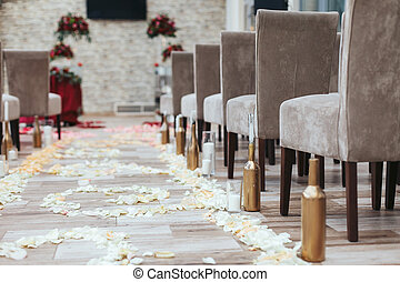 Aisle in the hall between brown chairs with white petals on...