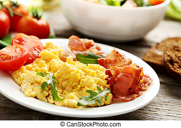 Scrambled eggs with bacon and vegetables on a grey wooden table