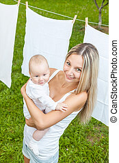 Beautiful mother and baby playing together outdoors -...