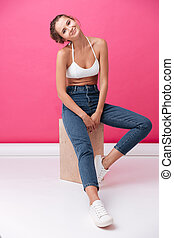 Funny pretty woman in white top and jeans sitting - Full...