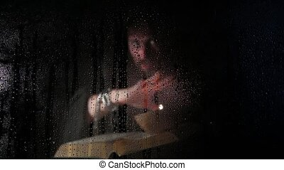 necromancer casts spells from thick ancient book by candlelight, behind transparent glass covered by water drops on a dark background