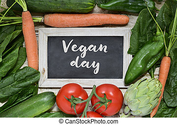 vegetables and text vegan day - high-angle shot of a wooden...