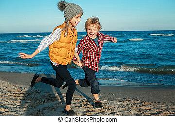friends siblings running on beach