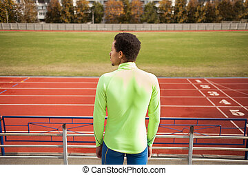 Sprinter stands in the stadium. The dark-skinned man in...