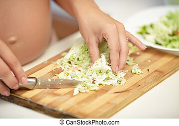pregnant woman cuts cabbage on wooden Board, close-up -...