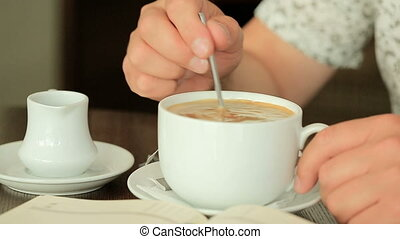 man mixing sugar in coffee cup, close up