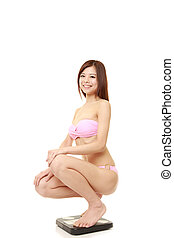 young Japanese woman on a weight scale smiles - portrait of...