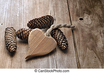 wooden heart shaped and pine cones on a wooden table