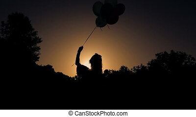 silhouette of woman with balloons on sky background