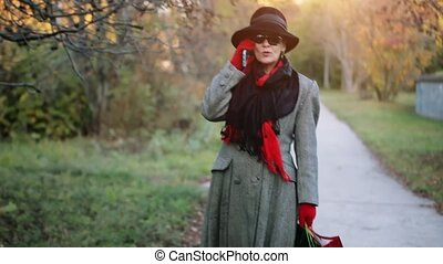 Attractive elegant woman 50 years old with mobile phone in the autumn park going from shopping with colorful bags. 1920x1080