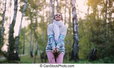 Happy young woman wearing knitted sweater throwing leaves in...