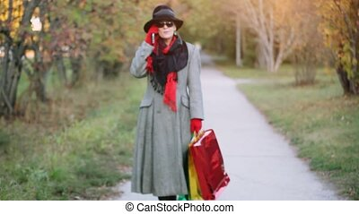 Attractive elegant woman 50 years old with mobile phone in the autumn park going from shopping with colorful bags.