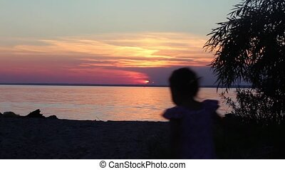 silhouette of a young girl on the beach at sunset