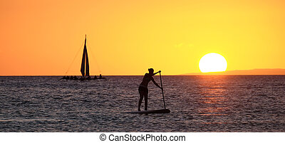 Silhouette of a girl floating on on the sup surfboard at...
