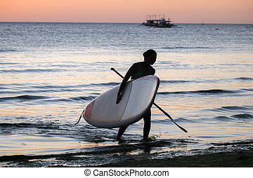 Silhouette of a girl with the sup surfboard at sea beach of...