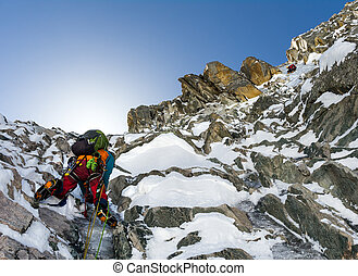 climbers at the mountain summit in scenic Tian Shan range in...