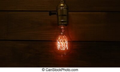 The Old vintage Edison's light bulb glowing on background of...