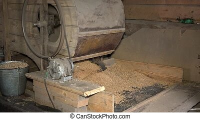 Retro automatic handmade machine sifting grain in barn. Closeup