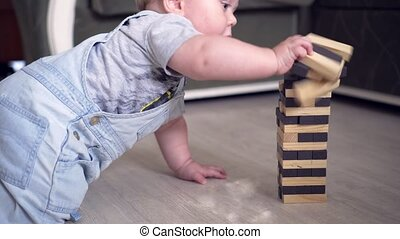 Baby boy destroing jenga tower with wooden building boards.