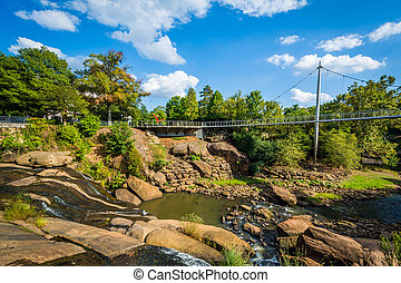 Bridge and waterfall at the Falls Park on the Reedy, in...
