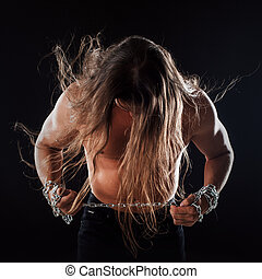 Young man with long hair breaks the iron chain, leaned...