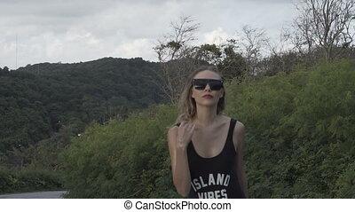 Pretty woman walking in black swimwear - Front view of...