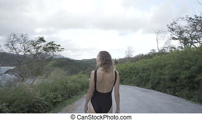 Pretty woman walking in black swimwear
